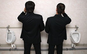 two-businessman-talking-on-phone-at-urinals